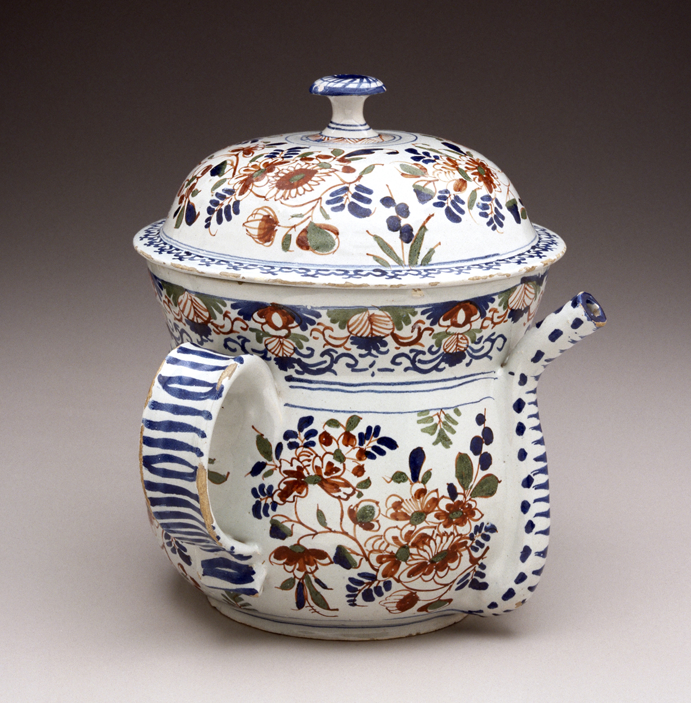 A small white lidded pot with a spout and handle. The white surface is painted with red, green, and blue decorations.